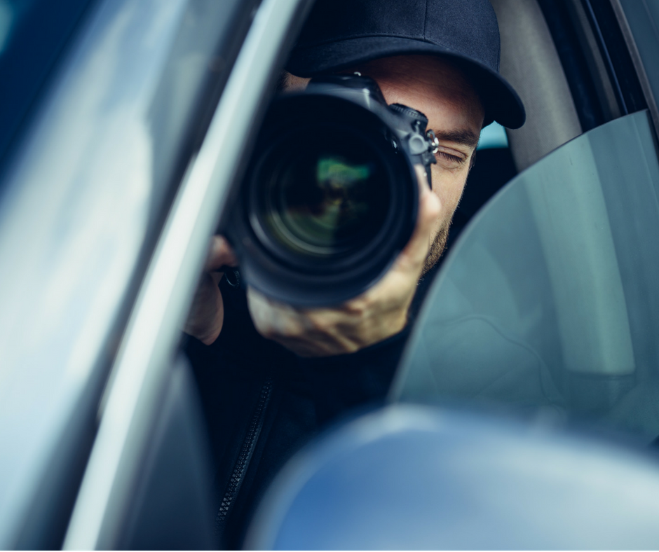 Private investigator using a telephoto lens to capture spouse affair