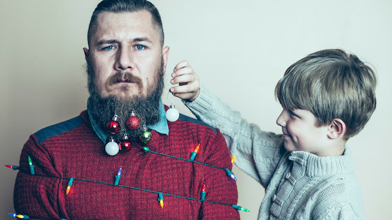 Single dad with son hanging ornaments on beard